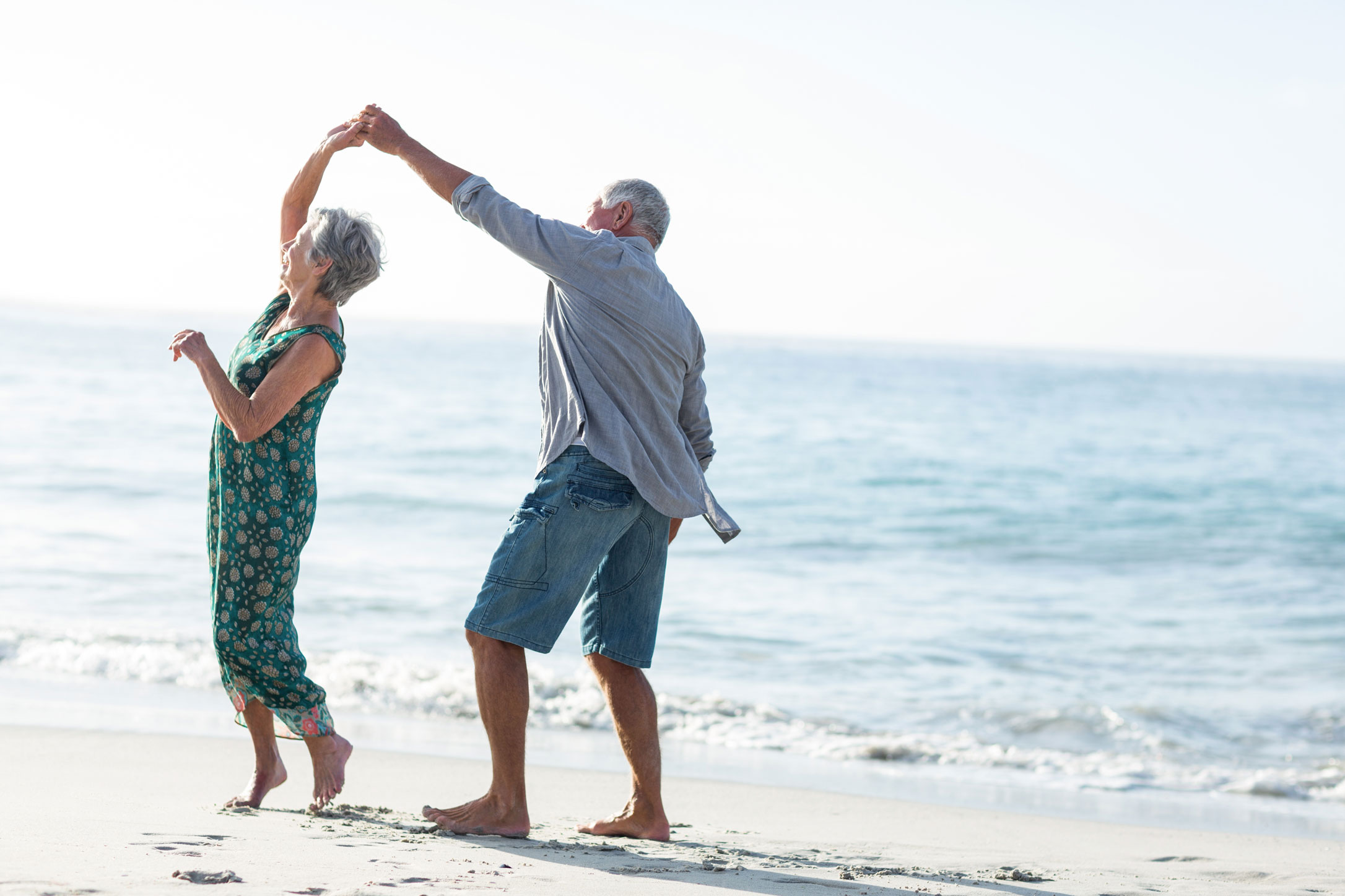 An elderly couple dancing on sunny Fort Lauderdale Beach.